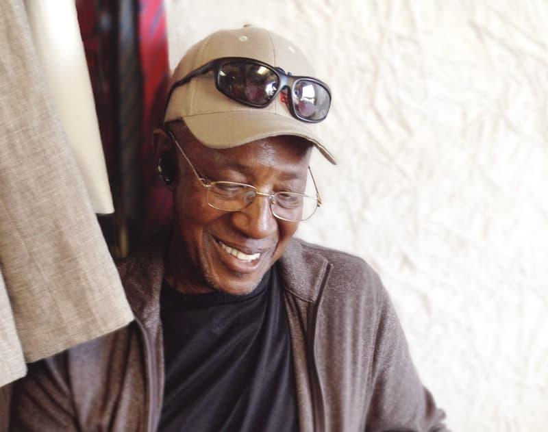 Old man with hearing aid smiling